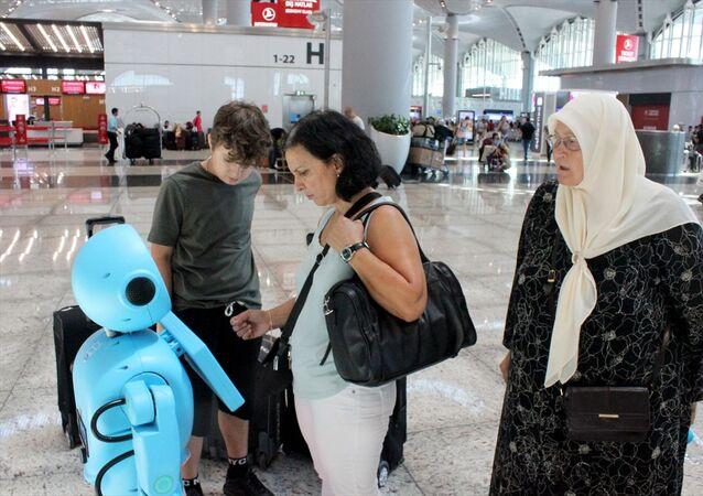 İstanbul Havalimanı'nda yolculara yardım etmesi ve yol göstermesi için Dış Hatlar Gidiş Terminali'ne konulan test aşamasındaki yerli iki robot, yolculardan ve çalışanlardan yoğun ilgi gördü. Eşiyle birlikte ailesini Norveç'e uğurlamaya gelen 72 yaşındaki Fahriye Gürsoy (sağda), İngilizce ve Türkçe olarak hizmet veren robotları deneyenler arasında yer aldı.