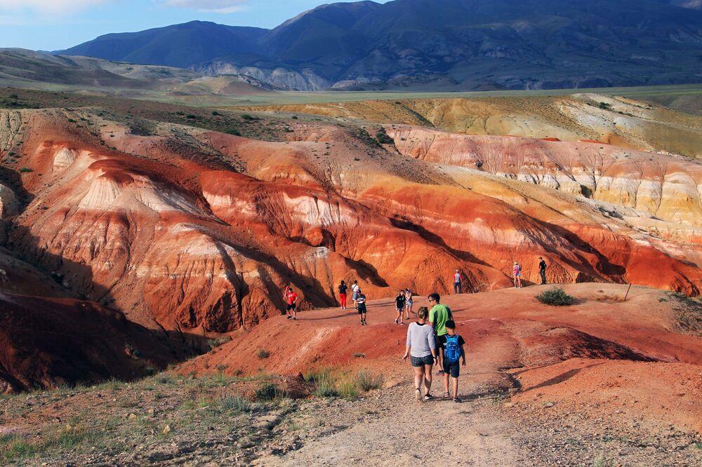 Altay'da yer alan ve Mars vadisi olarak bilinen Kızıl-Çin vadisini görmeye gelen turistler.  Kaya oluşumlarında büyük miktarda bulunan cıva, bölgenin Mars'ı andıran manzarasının nedeni.