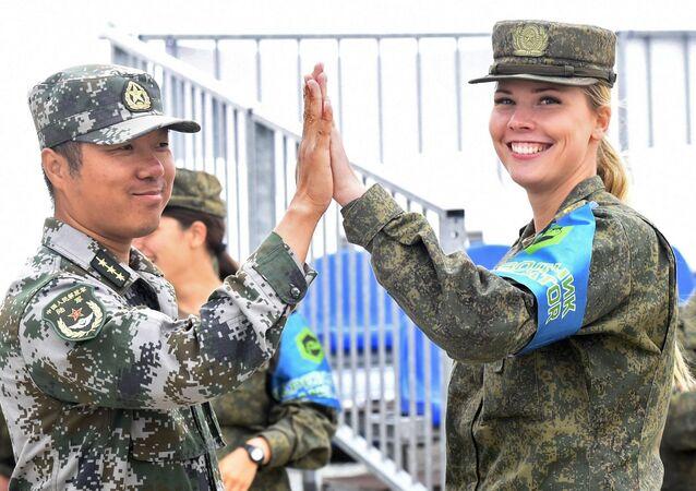 Rus kadın asker ile Çinli asker, Army-2019 Oyunları kapsamında düzenlenen yarışmanın yarı finali sırasında poz veriyor.
