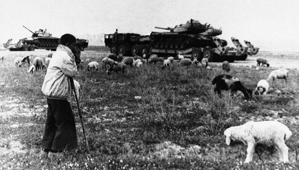 Genç çoban,  çatışmalarda yerle bir edilmiş İran'ın Ahvaz kentinin çevresindeki tankları izliyor, Nisan 1981
