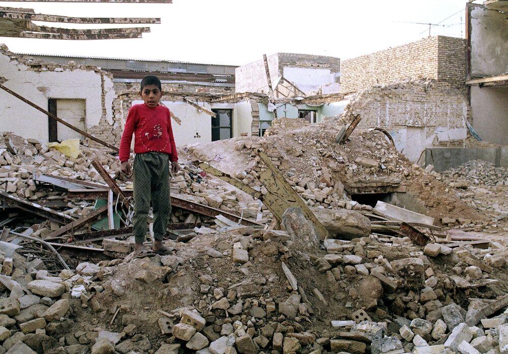 Iranlı çocuk, Irak'ın  25 Ocak 1987 tarihinde Ahvaz'da  düzenlediği hava saldırısı sonucunda yıkılmış olan evinin enkazlarınan duruyor.