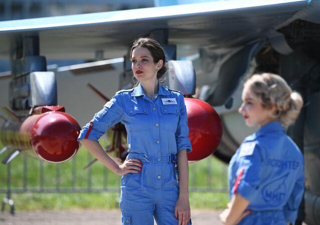 Rusya'nın Moskova bölgesinde düzenlenen Uluslararası Havacılık Fuarı MAKS-2019'da çok amaçlı MiG-35 avcı uçağının yanında poz veren hostesler.