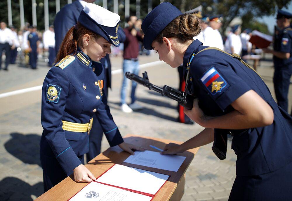 Krasnodar Askeri Havaclık Okulu'nda  kadın öğrenciler için düzenlenen yemin törenine katılan öğrencilerden biri imza atıyor.