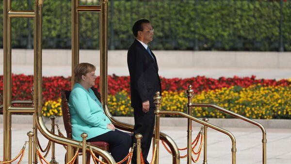 Resmi törenlerde titreme nöbeti geçirmesiyle dikkat çeken Almanya Başbakanı Angela Merkel, Çin Başbakanı Li Keqiang'ın karşılama töreninde Çin milli marşı çalınırken oturdu. - Sputnik Türkiye