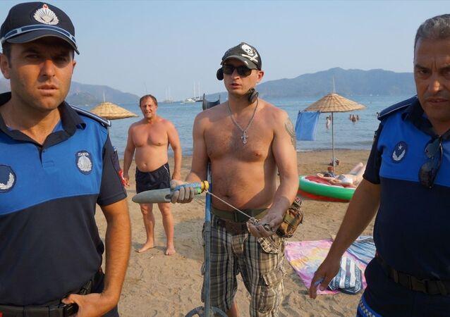 Muğla'nın Marmaris ilçesindeki plajda Rus turistin dedektörle arama yapması vatandaşları şaşırttı. Şikayet üzerine plaja gelen zabıta görevlilerinin uyardığı turist, Sahildeki kumlara atılan metal çöpleri dedektör ile temizliyorum. dedi.