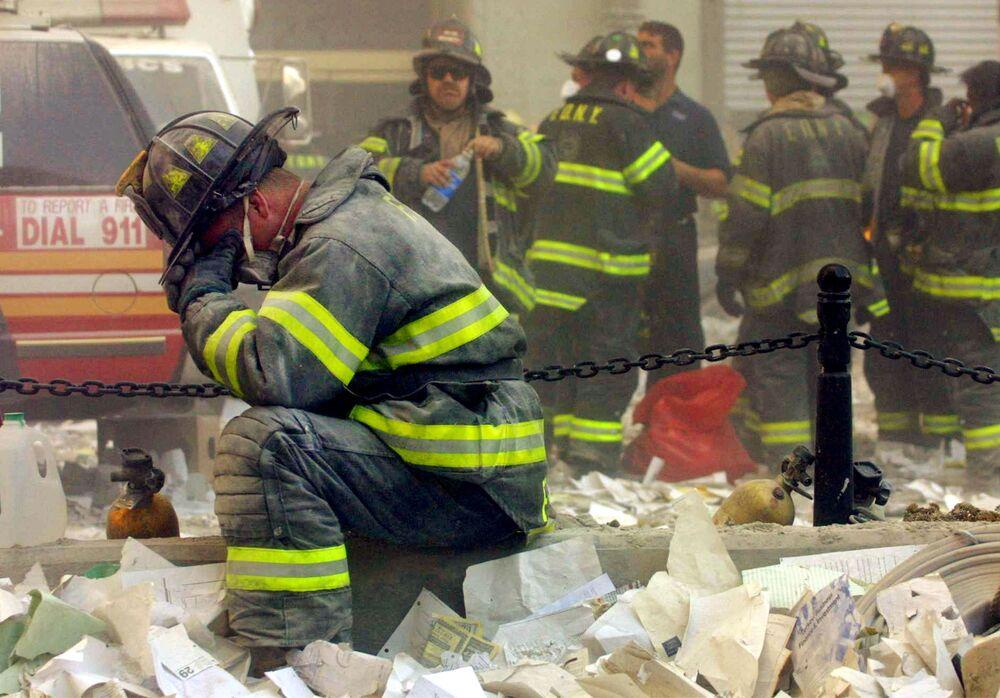 New York'taki Dünya Ticaret Merkezi'ne ait kulenin çöktüğü alanda yangın söndürme çalışmalarını yürüten itfaiyecilerden biri ağlıyor.
