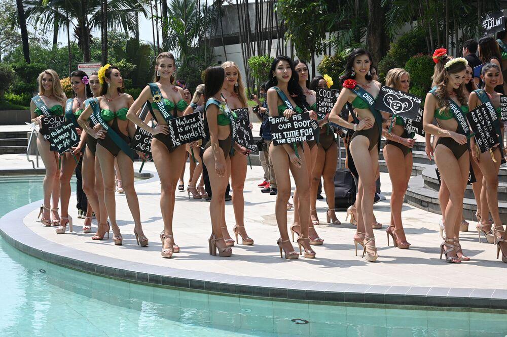 Manila'daki çekime katılan Miss Earth 2019 adayları, üzerinde çevreci sloganlar yazılı  pankartlar ile poz verdi.