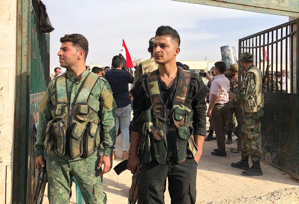 Menbiç kentinde kontrolü sağlayan Suriye hükümet güçlerinin askerleri.