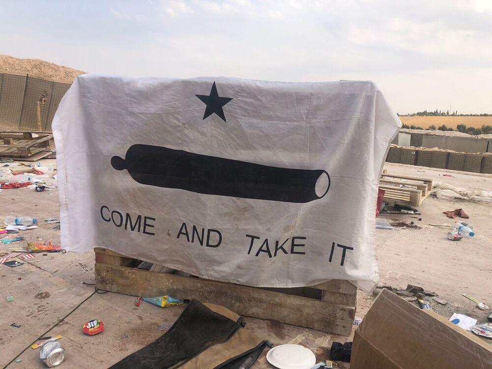ABD'li askerlerin terkettikleri Menbiç'teki hava üssünde görüntülenen Come and take it (Gel ve Al Bunu) sloganlı bayrak.