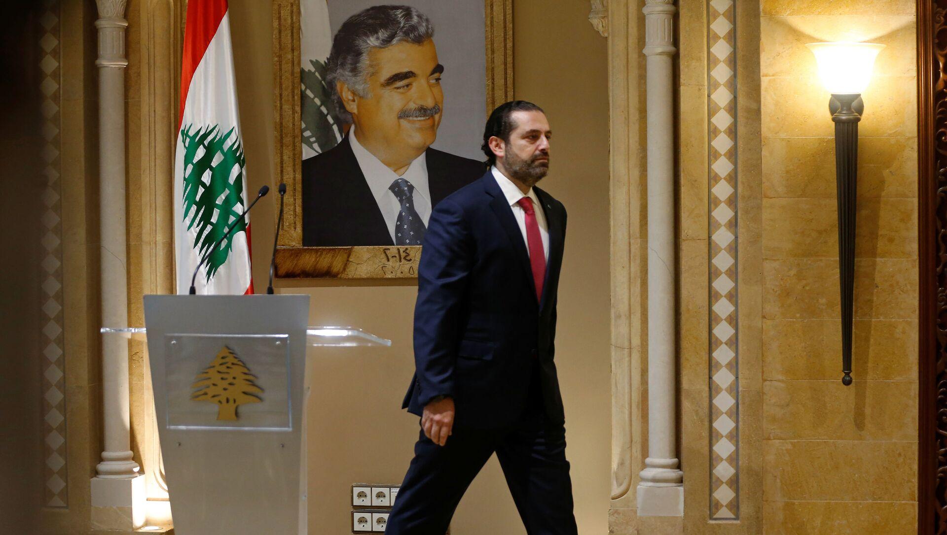 Suikasta kurban giden babası Refik Hariri'nin portresi önünde başbakanlıktan istifasını sunacağını açıklayan Saad Hariri, salondan çıkarken - Sputnik Türkiye, 1920, 15.07.2021
