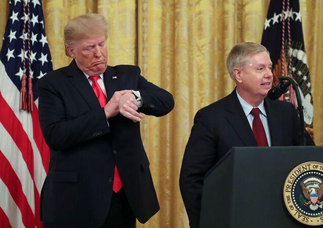 'Türkiye'ye yaptırım' mektubu gönderen senatörlerden Cumhuriyetçi Graham Beyaz Saray'da konuşurken arkasındaki Trump saatine bakıyor.