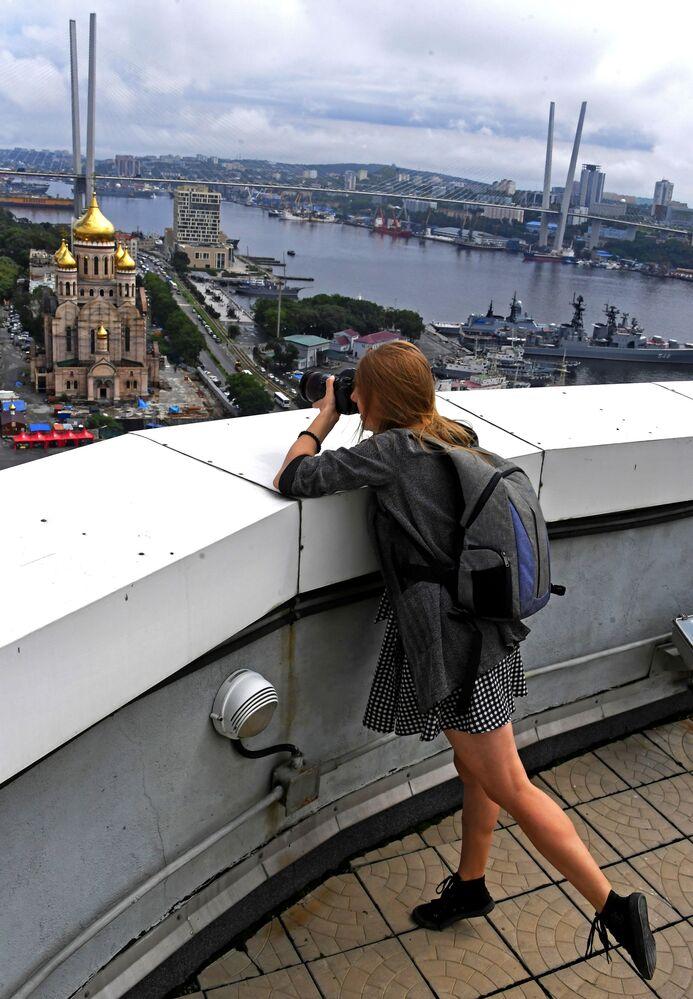 Vladivostok  Fotoğrafta: Şehir manzarasının görüntüsünü çeken bir kadın.