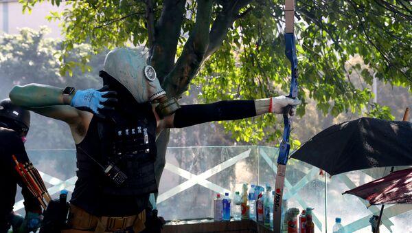 Hong Kong Polytechnic Üniversitesi'nde (PolyU) işgal eylemi düzenleyenlerden biri polisle çatışmalarda ok atarken - Sputnik Türkiye