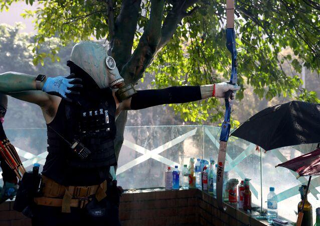 Hong Kong Polytechnic Üniversitesi'nde (PolyU) işgal eylemi düzenleyenlerden biri polisle çatışmalarda ok atarken