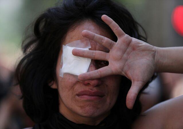 Şili başkenti Santiago'daki eylemlerde polisin insanları gözlerinden vurmasını protesto için göz bandı takan bir gösterici