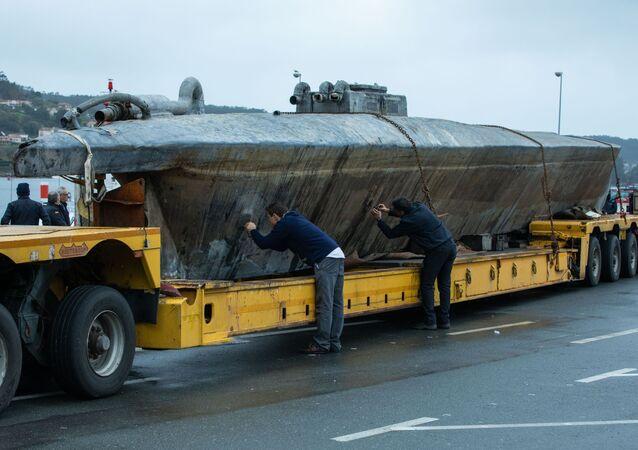 İspanya'nın kuzeybatısındaki Aldan'da yetkililer kaçak uyuşturucu sokarken yakalanan denizaltıda incelemelerde bulunuyor.