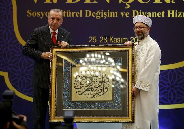 Türkiye Cumhurbaşkanı Recep Tayyip Erdoğan, Diyanet İşleri Başkanlığı tarafından bir otelde düzenlenen 6. Din Şurası Kapanış Programı'na katıldı. Programda Diyanet İşleri Başkanı Prof. Dr. Ali Erbaş, Cumhurbaşkanı Erdoğan'a hat sanatıyla yazılmış Kuran-ı Kerim ayetinin bulunduğu bir tablo hediye etti.