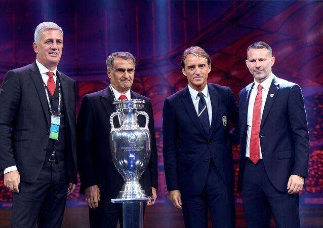 Şampiyona tarihinde ilk kez 12 ülkenin ev sahipliği yapacağı, 12 Haziran-12 Temmuz tarihlerinde düzenlenecek 2020 Avrupa Futbol Şampiyonası'nın (EURO 2020) kura çekimi Romanya'nın başkenti Bükreş'teki ROMEXPO Sergi Merkezi'nde yapıldı. Kura çekimi törenine A Milli Futbol Takımı Teknik Direktörü Şenol Güneş (sol 2), İtalya teknik direktörü Roberto Mancini (sağ 2) ve Galler teknik direktörü Ryan Giggs de (sağda) katıldı.