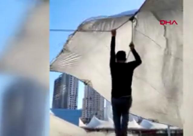 Kadıköy'de pazarcı çadır kurarken ip koptu. Şiddetli, rüzgar nedeniyle havalanan çadırın ipini bırakamayan pazarcı metrelerce yükseldi. O anlar cep telefonu kamerasına yansıdı.