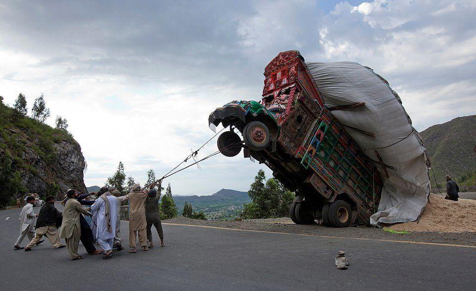 Pakistan'ın başkenti İslamabad'ta 13 Nisan 2012'de çekilen bu karede  bir grup adam aşırı yüklenmiş bir kamyonun içindeki buğdayları boşaltmak adına kamyonu iplerle çekerek yönlendirmeye çalışıyor.