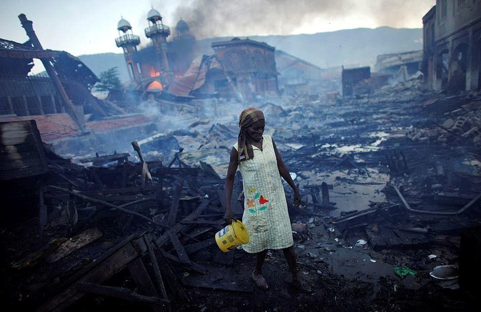 Yaklaşık 300,000 kişinin öldüğü bir o kadar yaralının olduğu 2010 Haiti depremi sonrası başkent Port-au- Prince'deki  pazar alanında bir kadın.  Söz konusu Pazar yeri 2008 yılında çıkan yangında küle dönmüştü.