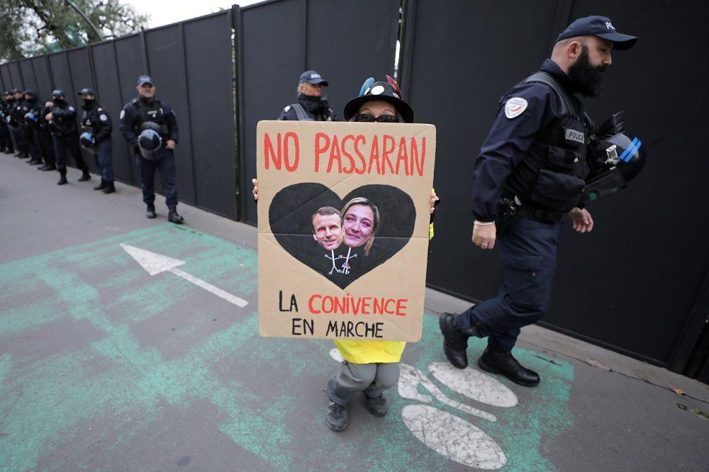 Protestoculardan biri Cumhurbaşkanı Macron ile sağcı lider Marine Le Pen'in birarada olduğu bir pankart taşıyor.