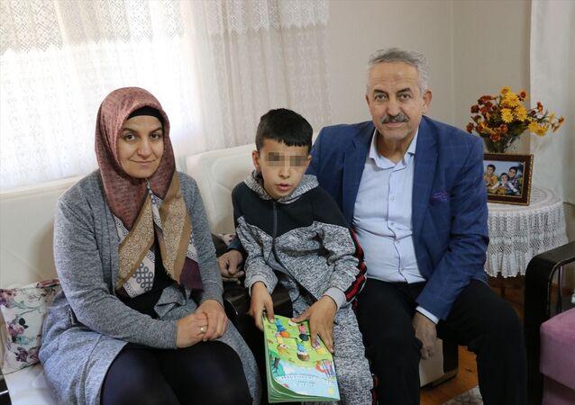 Denizli'nin Tavas ilçesinde yaşayan otizmli A.E'nin (ortada) dedesi Ahmet Ç., çocuğun sesinden rahatsız olduğunu ileri sürerek elinde bıçakla kapıya gelip hakaret ettiği iddiasıyla üst komşuları hakkında şikayetçi oldu