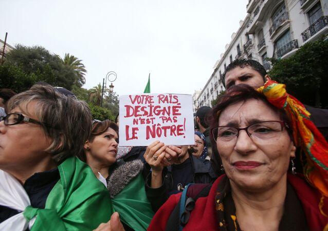 Cezayir'de seçim sonucu ve yeni devlet başkanının açıklanmasının ardından sokaklara dökülenler arasında Sizin devlet başkanınız bizim değil dövizi taşıyan grup