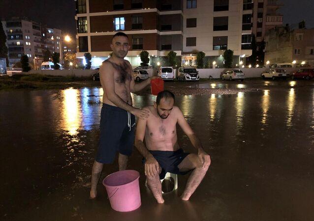 İzmir'de su kesintisine dikkati çekmek için yağmur suyuyla sokakta yıkandılar