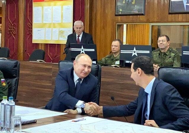 7 Ocak 2020'de Şam'ı ziyaret eden Putin, Esad'la Suriye'deki Rus askeri yetkililerinden brifing almaya el sıkışarak başladı.