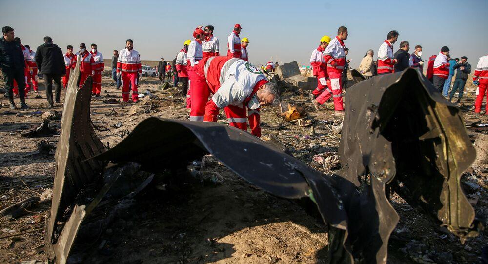 İran Kızılayı çalışanları Tahran'da düşen Ukrayna yolcu uçağının enkazında incelemelerde bulunurken