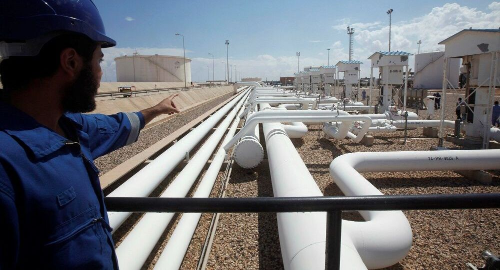 A worker gestures towards pipelines at the port and Zawiya Oil Refinery