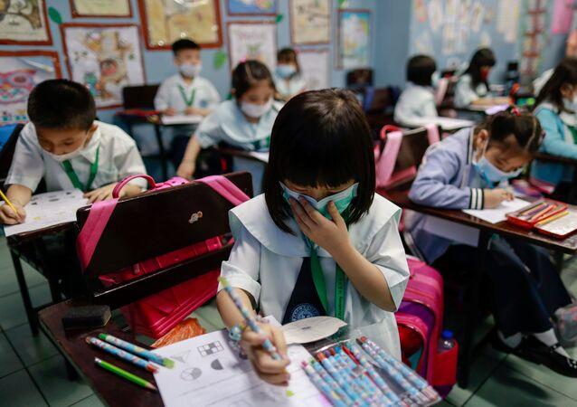 Filipinler'de Çinlilere eğitim veren okulda öğrenciler maske takarak derslere katılıyor.