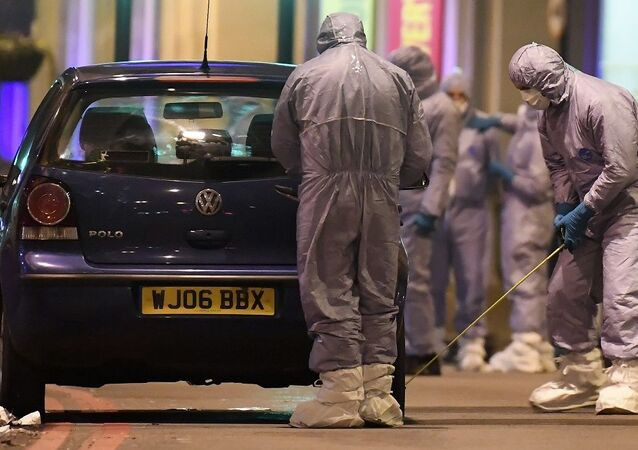 Police forensic officers work near a car at the scene after a stabbing incident in Streatham London