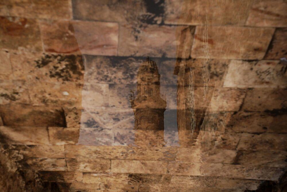 Ulu Cami'nin taşlı sokakta biriken sudaki yansıması.