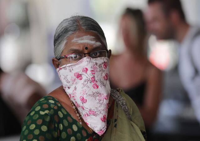 Sri Lanka'daki Katunayake Uluslararası Havalimanı'nda şalı maske olarak kullanan Hintli bir kadın.