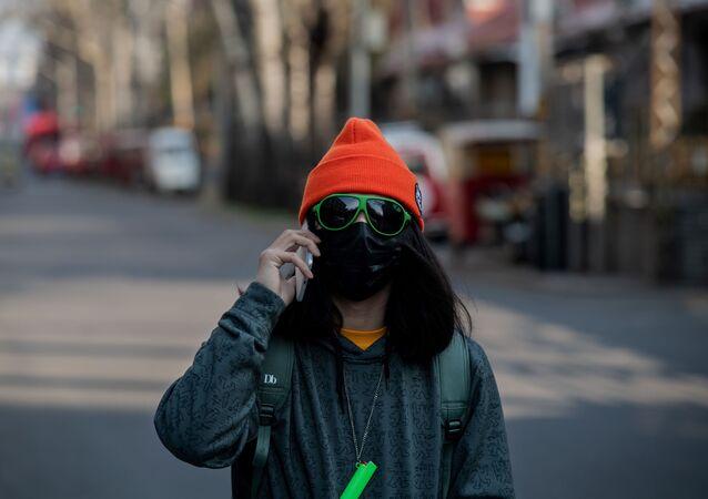 Maske ve gözlük takan genç kadın, Pekin'de sokaktan geçerken.