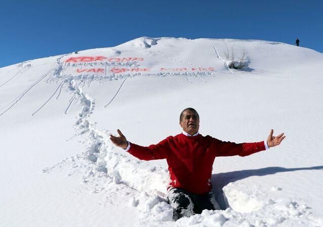 Hakkari'nin Demirtaş köyündeki 2 bin 800 rakımlı karla kaplı dağa çıkan Aydın, köylülerle birlikte okuduğu şarkının klibinde kuru otlarla üzerini kamufle edip, yer yer 1,5 metreyi bulan karda yürüdü.