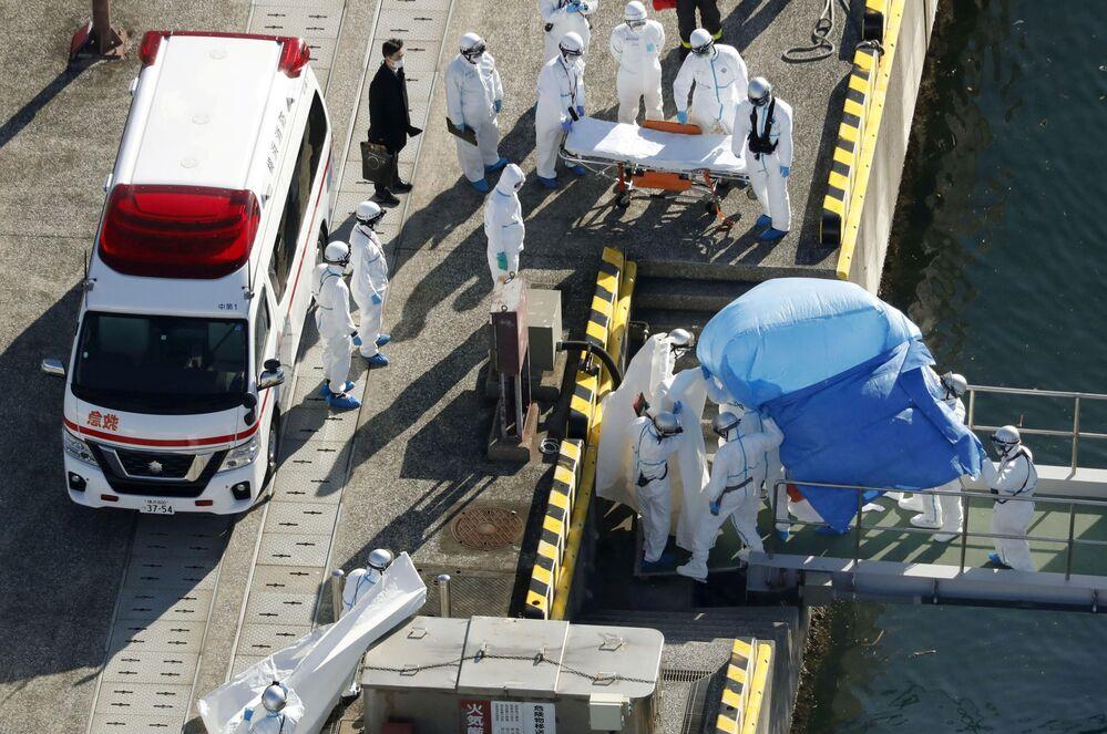 Koruyucu kıyafetli Japon polis  görevlileri, Japonya'nın Yokohama limanında günlerdir karantina altında bulunan  'Diamond Princess' adlı lüks yolcu gemisinin koronavirüs saptanmış yolcusunu  ambulansa yerleştirmeye hazırlanıyor.