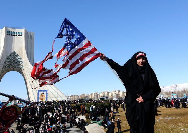 Tahran'daki Azadi Meydanı'nda İran İslam Devrimi 41. yıldönümü törenleri sırasında bir kadın yanmış ABD bayrağı sallarken