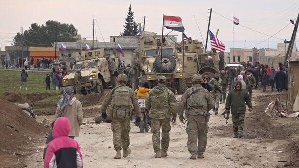 Suriye'nin Haseke bölgesinde Kamışlı yakınındaki Harbat-Hamo köyünde ABD'nin askeri konvoyunun yanından Ruslar ve Suriyeliler görülüyor. - Sputnik Türkiye