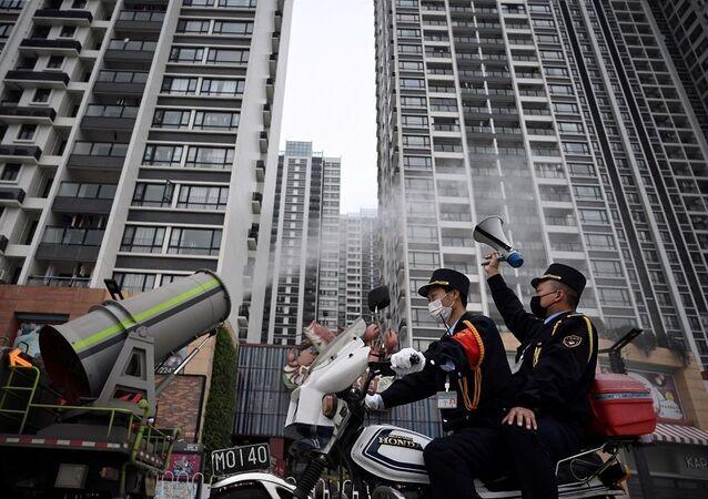 Çin'in Guangdong eyaletinin Guangzhou Panyu bölgesinde, yeni koronavirüs salgını sonrasında kamusal alanı dezenfekte eden bir aracın yanından geçen motorsiklet üzerinde elindeki hoparlörle duyuru yapan görevli