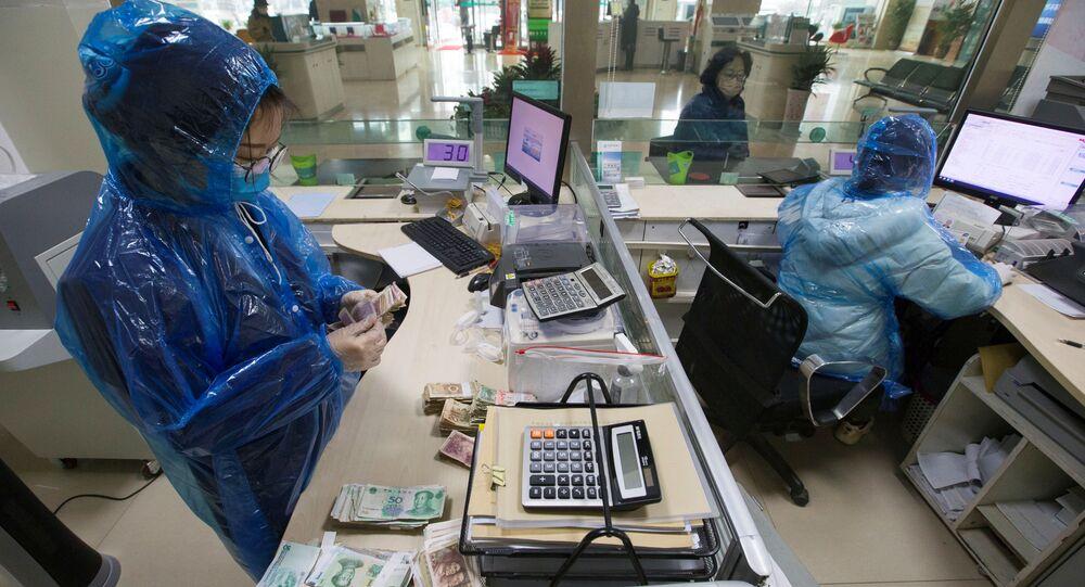 Koronavirüs salgınıyla mücadele eden Çin'de banka memurları koruyucu kıyafetler giyerek çalışıyor ve para sayıyor.