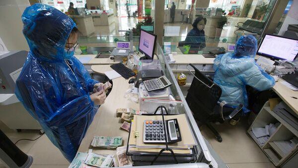 Koronavirüs salgınıyla mücadele eden Çin'de banka memurları koruyucu kıyafetler giyerek çalışıyor ve para sayıyor. - Sputnik Türkiye