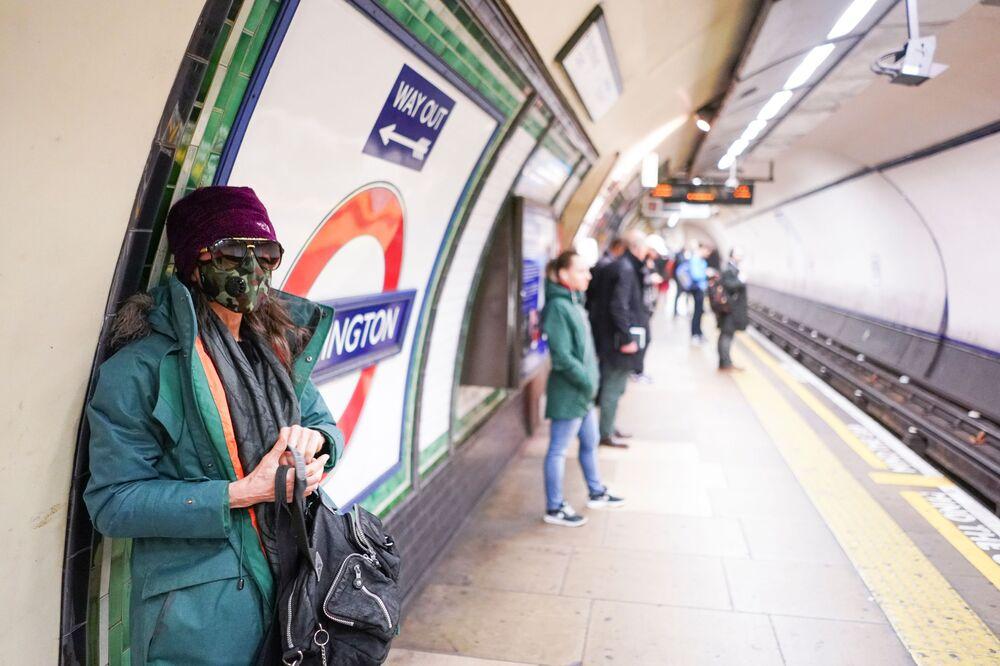 İngiltere'nin başkenti Londra'daki metroda maske takan bir kadın.