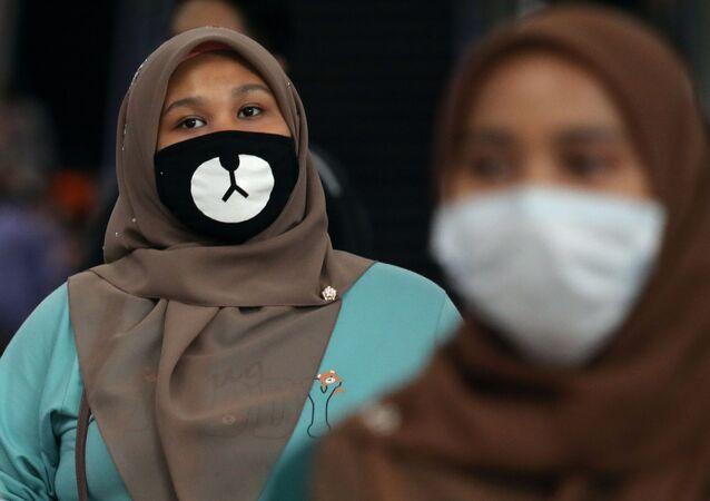 Malezya'daki bir tren istasyonunda maskeli kadın.