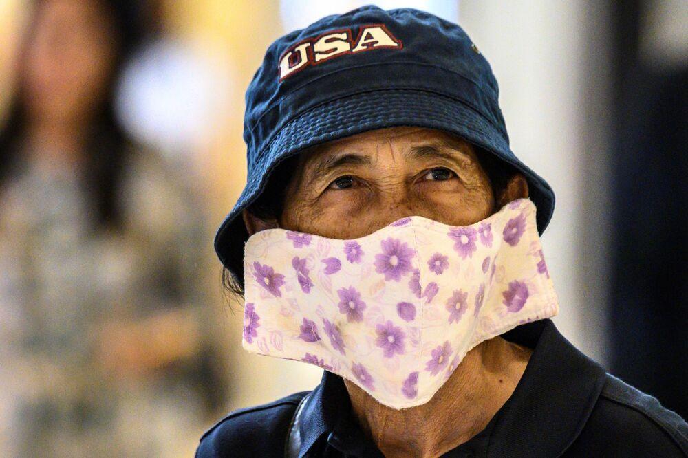 Tayland'ın başkenti Bangkok'ta bir AVM'de dolaşan maskeli bir kadın.