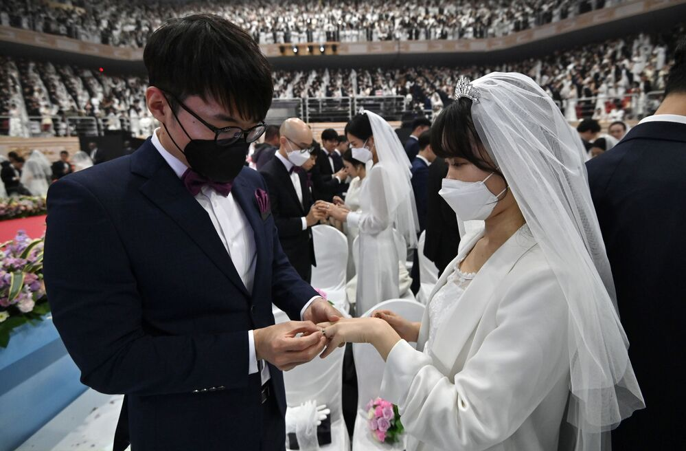 Güney Kore'de düzenlenen toplu düğün töreninde maskeler takan çiftler.