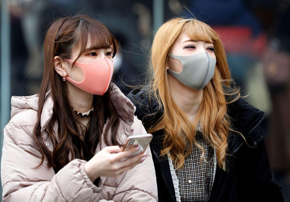 Koruyucu maske takan Tokyolu kadınlar.