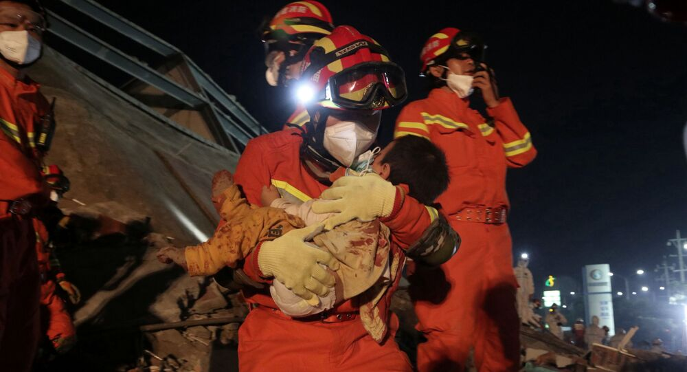A worker wearing a face mask rescues a child at the site where a hotel being used for the coronavirus quarantine collapsed, in the southeast Chinese port city of Quanzhou, Fujian province, China March 8, 2020. China Daily via REUTERS ATTENTION EDITORS - THIS IMAGE WAS PROVIDED BY A THIRD PARTY. CHINA OUT.